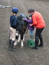 Helen helping a young rider onto her pony