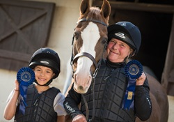 Two competition winners with blue rosettes and horse